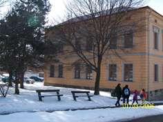 Foto z realizace - pohled na budovu, park, lavičky